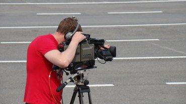 Ein Kamermann steht allein auf der Straße und schaut ins Objektiv